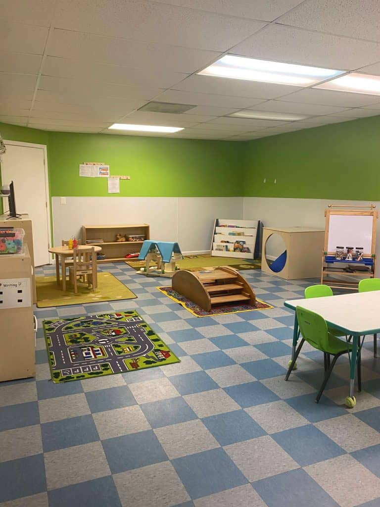 Daycare room with green walls and play areas on the ground