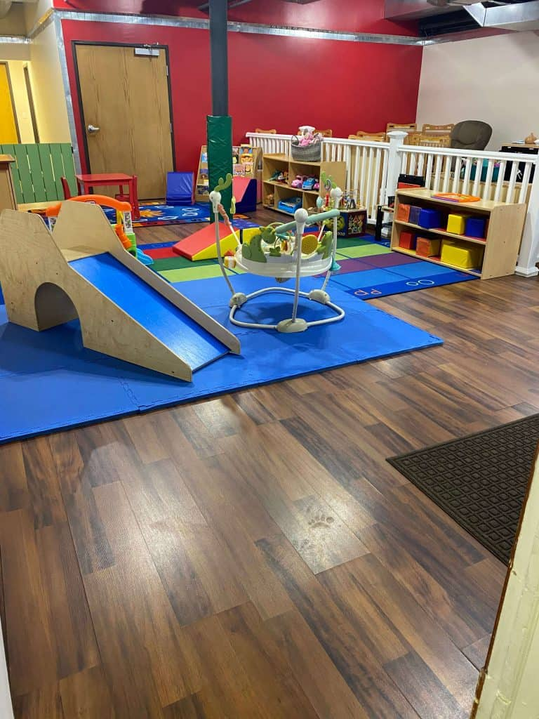 Daycare room with play structures and colored play items on the ground
