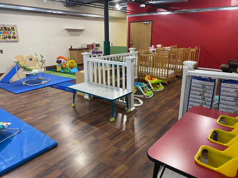 Daycare room with cribs and playstructures