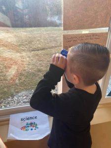 Preschool student holding binoculars to his eyes by the window