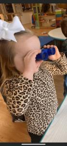 Preschool student holding binoculars to her eyes
