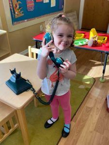 Preschool student holding a fake telephone to her ear