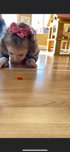 Young girl looking at an item that fell on the floor