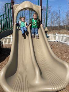 Preschool aged boy and girl sliding down a beige slide