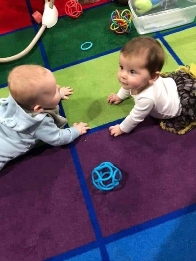 Two infants at daycare crawling on the ground on a colored rug