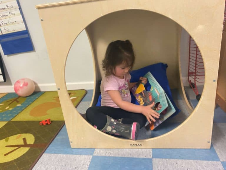 Young girl sitting inside a wooden play structure