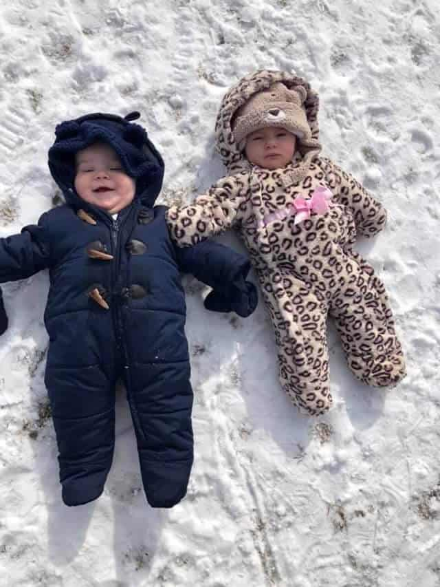 Two infants bundled in winter coats laying on snowy ground