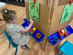 Preschool girl sitting and painting on green construction paper