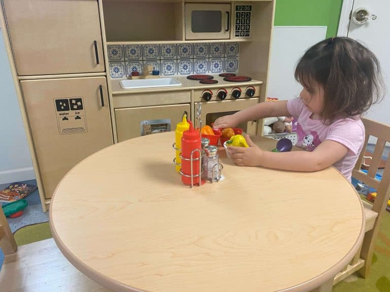 Young girl sitting at a round table playing with plastic food