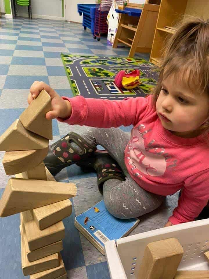 Young girl sitting on the ground playing with wooden blocks