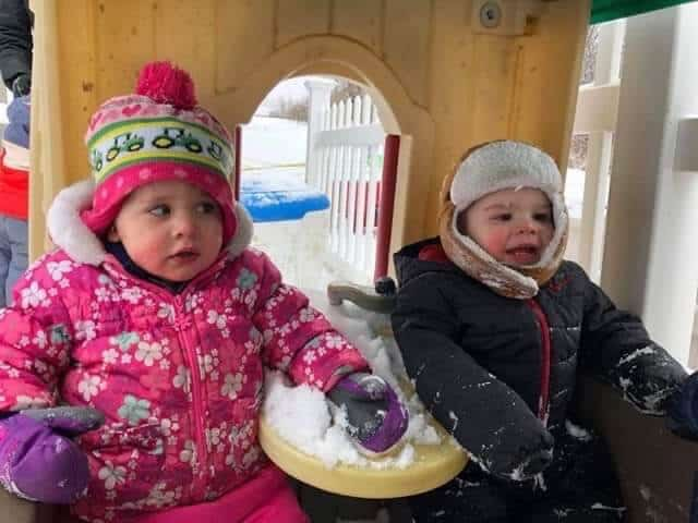 Two toddlers in winter coats sitting outside