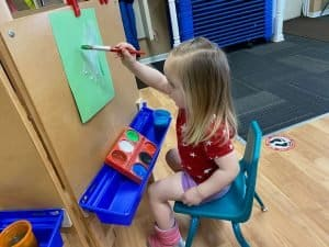 Preschool girl sitting in chair painting on green construction paper
