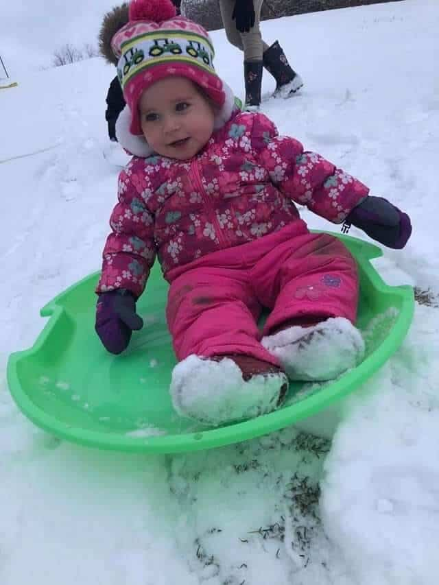 Toddler in winter clothes sledding down a hill on a green sled