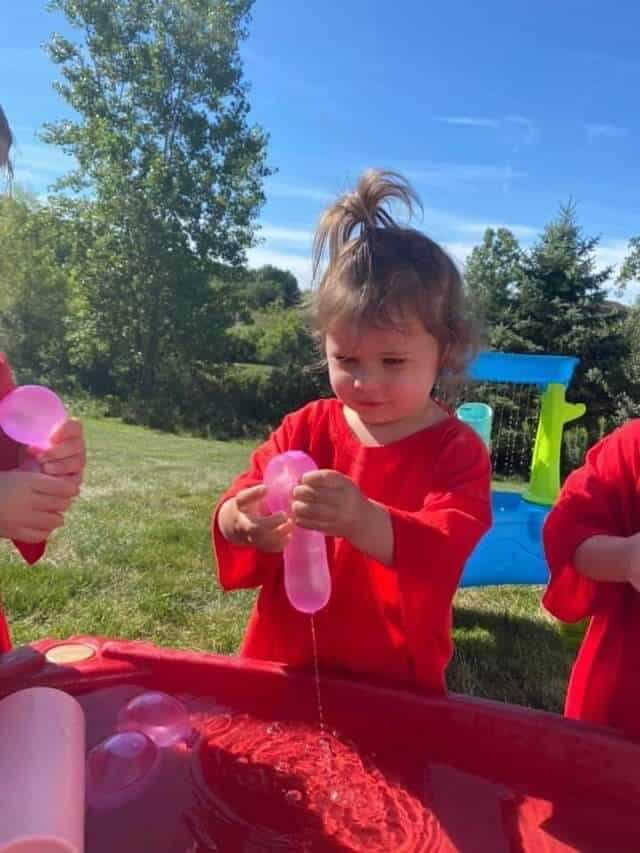 Young girl in red shirt playing with a pink water balloon